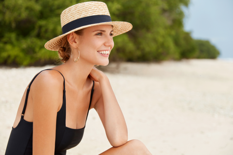 woman in straw hat and black swimsuit by the beach