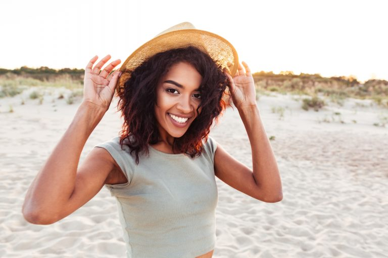 African American woman in hat on the beach
