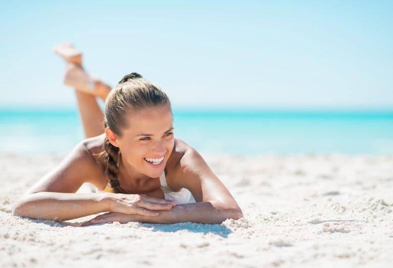 woman in swimwear lying on sand by the sea
