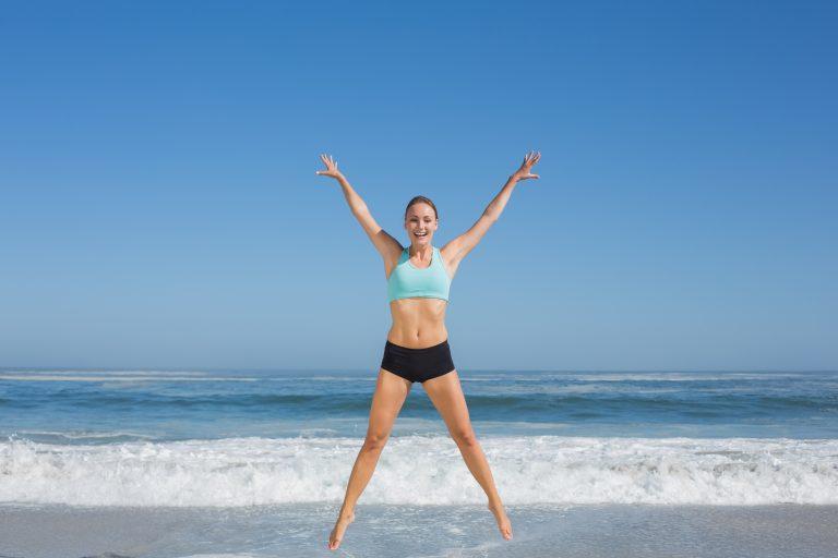 woman in yoga attire spreadeagle jump by the shore